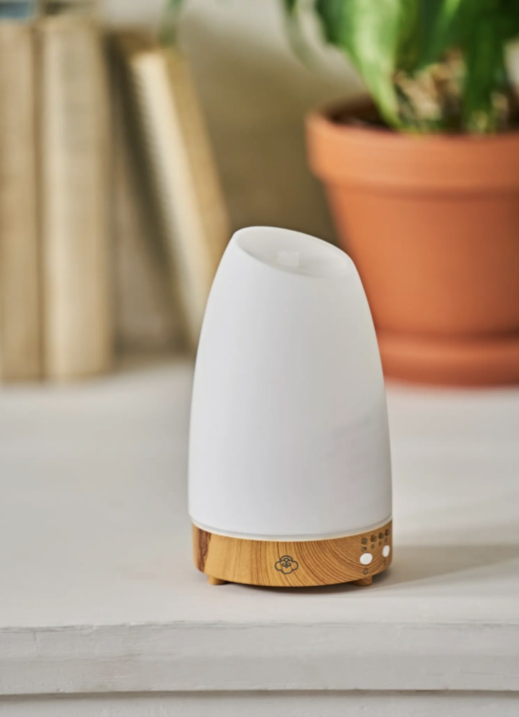 an aromatherapy diffuser with a white body and a wooden base resting on a ledge in front of books and a plant