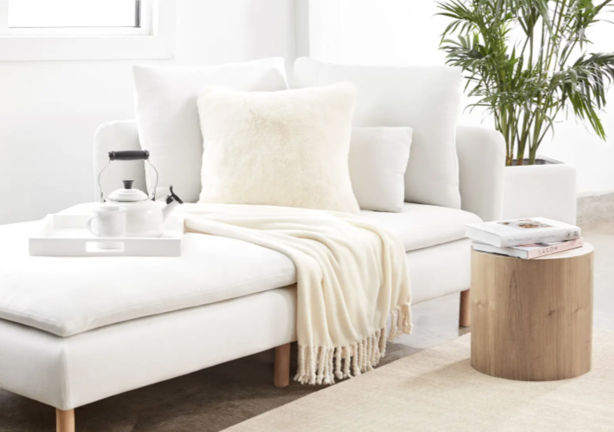 a vanilla throw draping over a couch in a living room