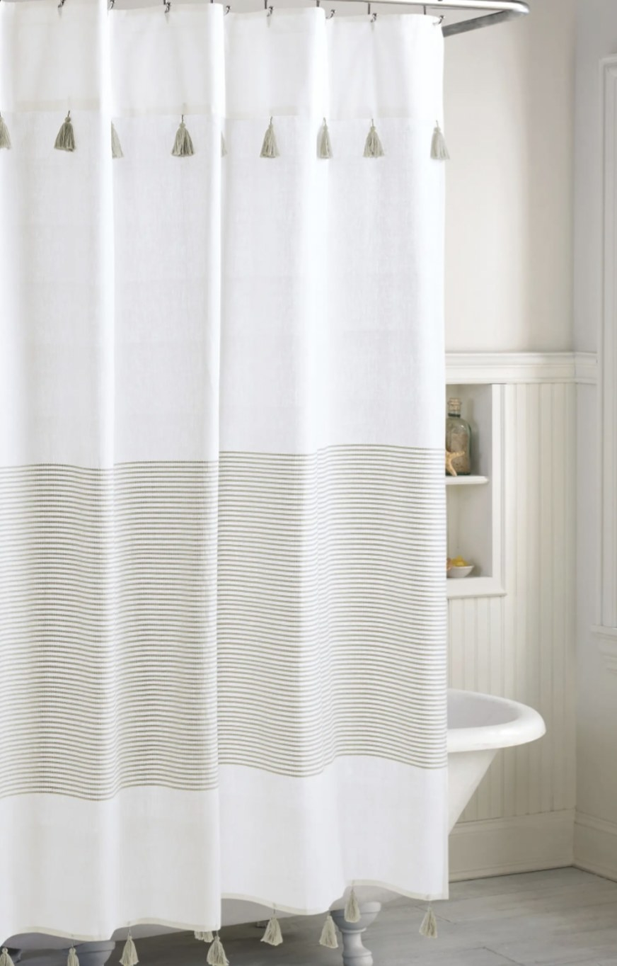 a shower curtain with tassles and vertical stripes