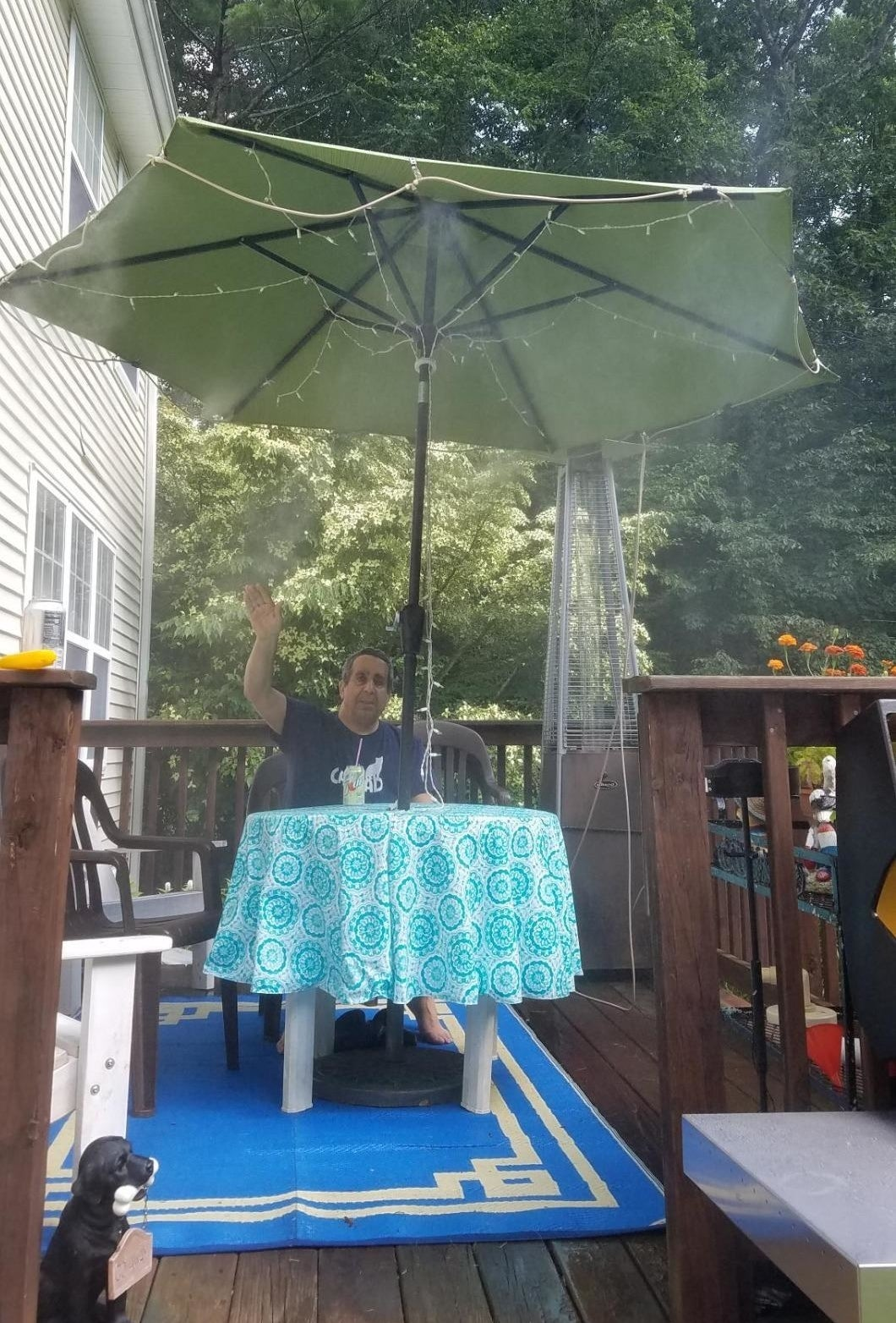 a reviewer sits on their patio under an umbrella with the orbit outdoor mist cooling system attached to it and spraying mist