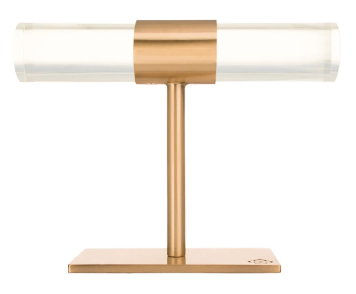 A T-bar jewelry stand with a rose gold base and acrylic bars