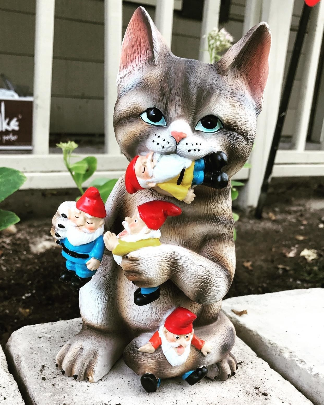 statue of tabby cat grabbing and eating small gnomes