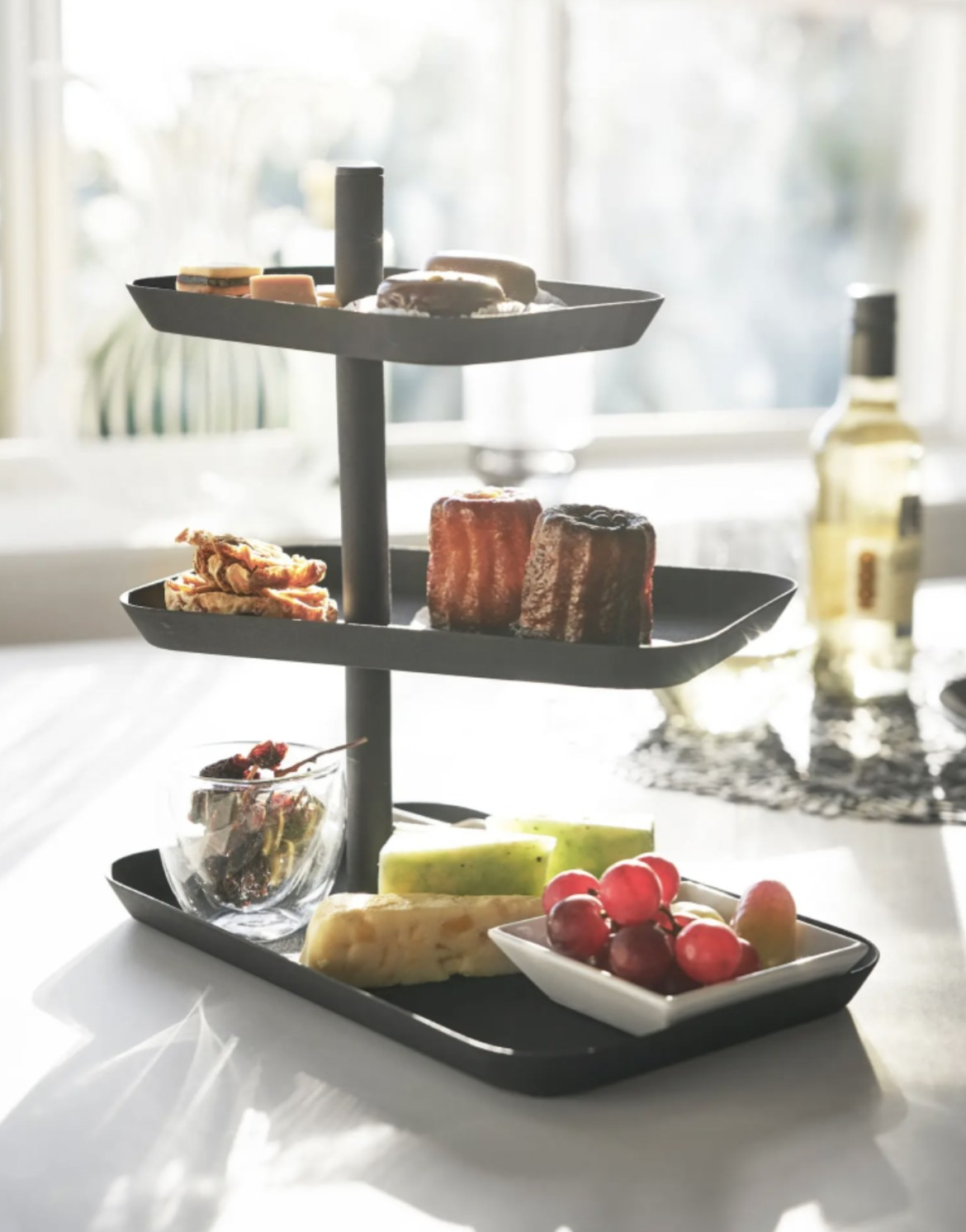 a three tier serving stand in black steel, holding fruits and desserts