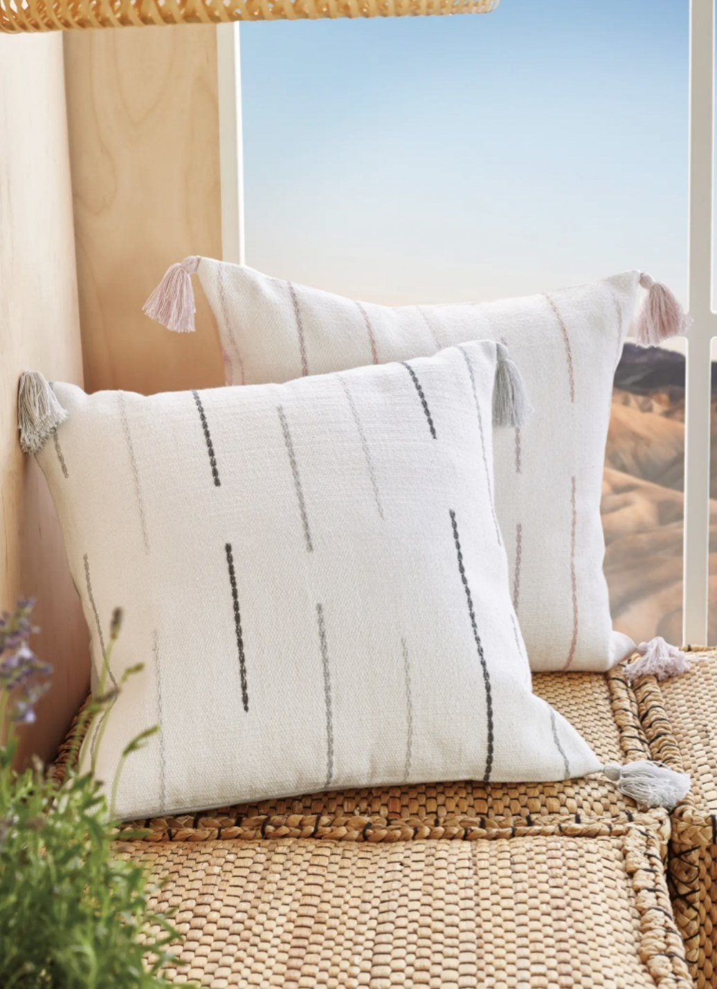 two embroidered accent pillow with tassles at its corners