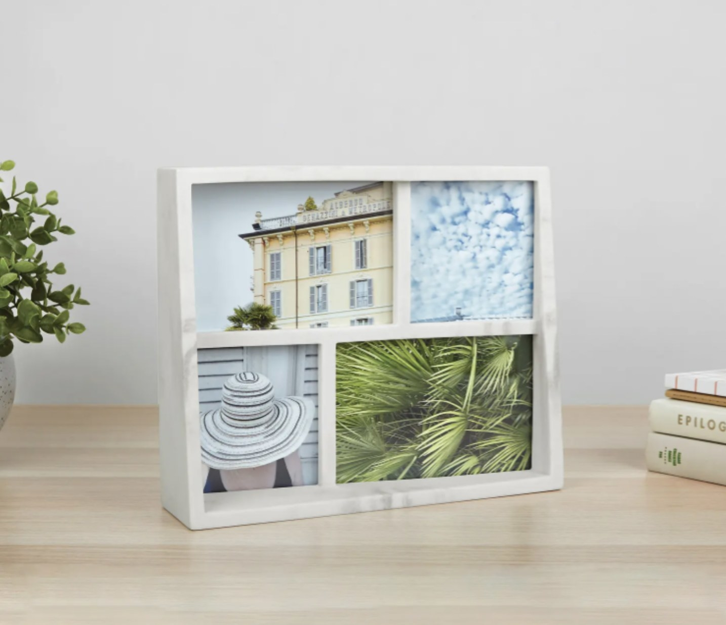 a marble picture frame that fits four photos resting on a counter