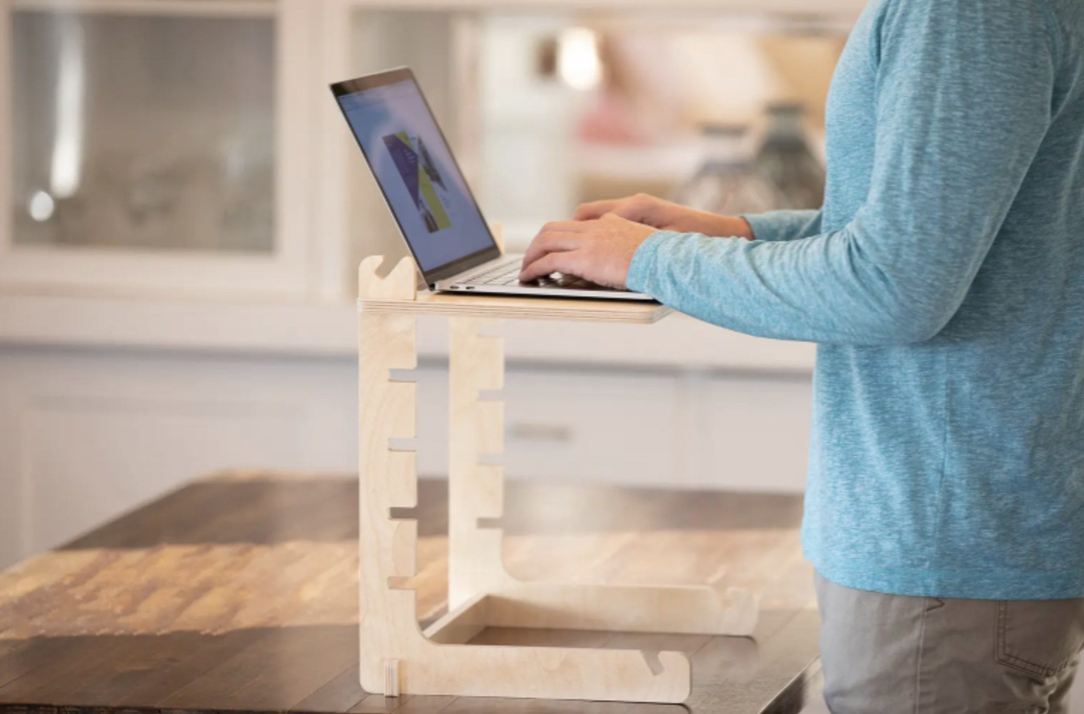 a person standing and working on their laptop that is supported by an adjustable desk stand made of wood