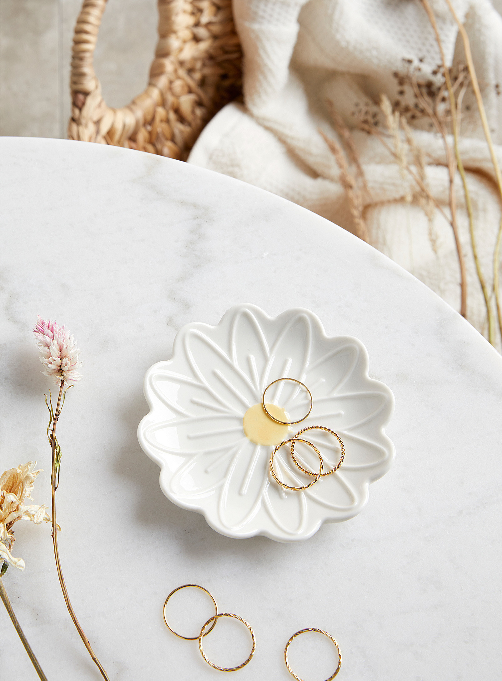 A flower-shaped ceramic trinket dish with rings on it