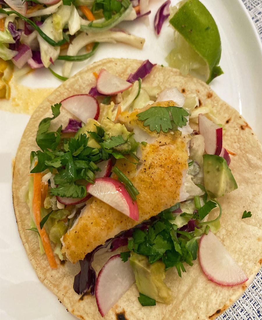 Crispy fish tacos topped with avocado, cilantro, and slaw.