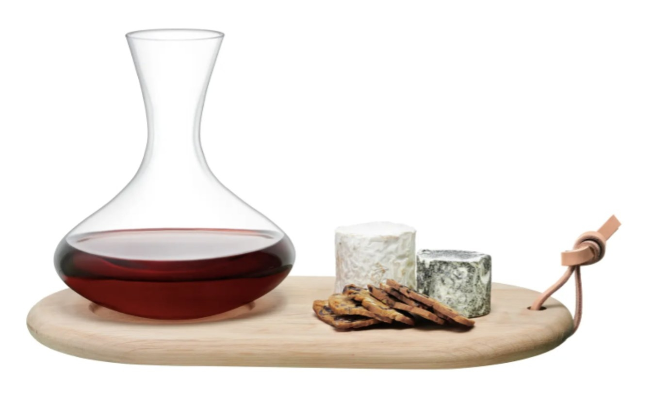 a wine carafe holding wine on top of a cheese board that is holding cheese and crackers
