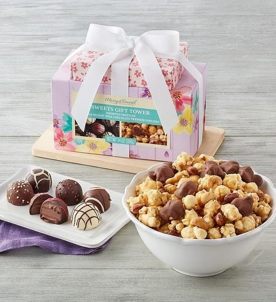 Floral gift box wrapped with bow with truffles and popcorn outside of it