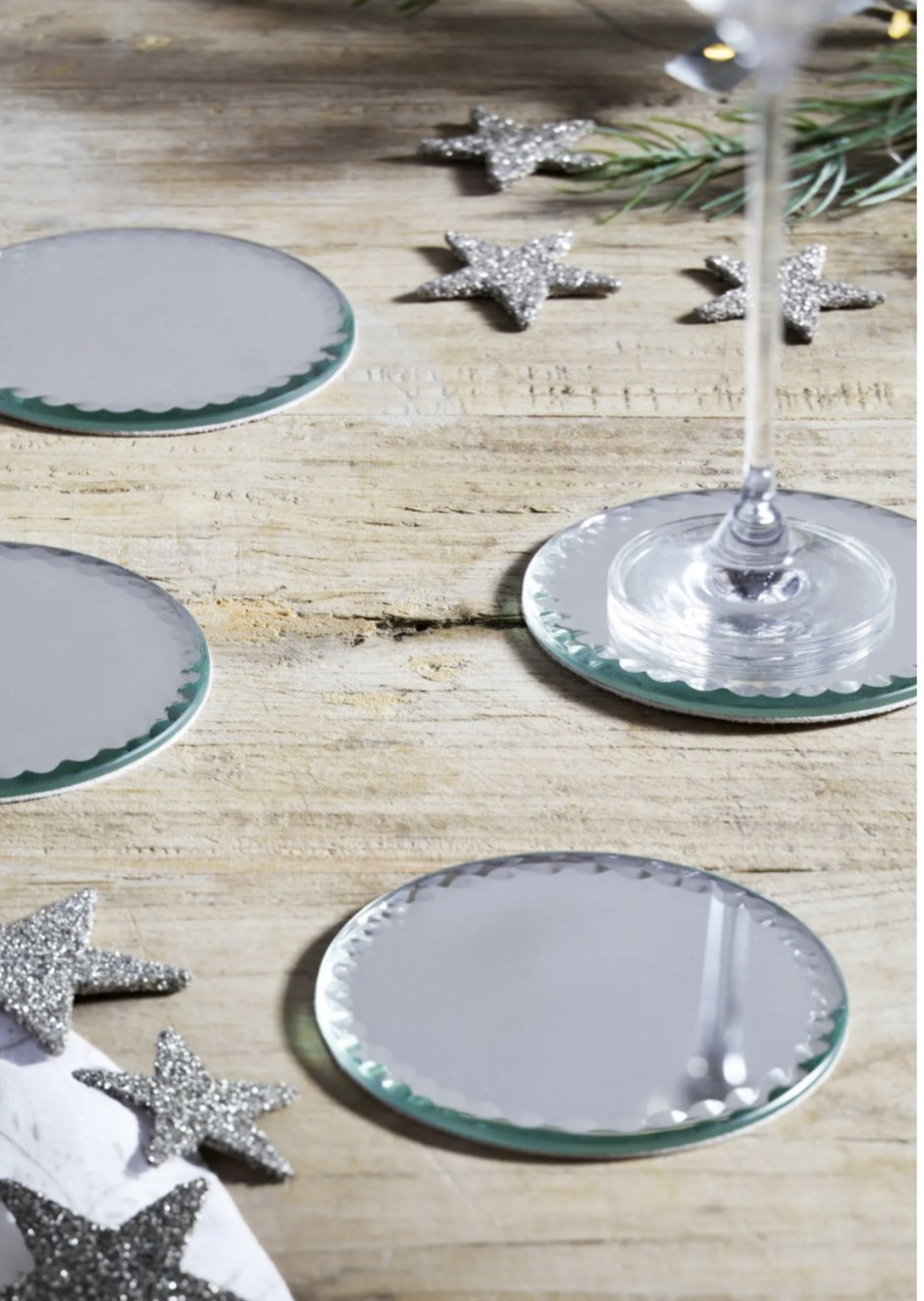 a set of four mirrored coasters on a table