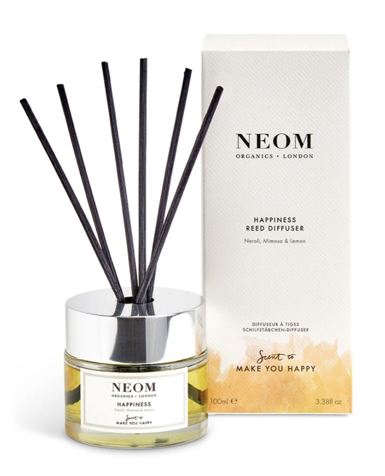 a reed diffuser with a glass bottle and silver lid with diffusers inside