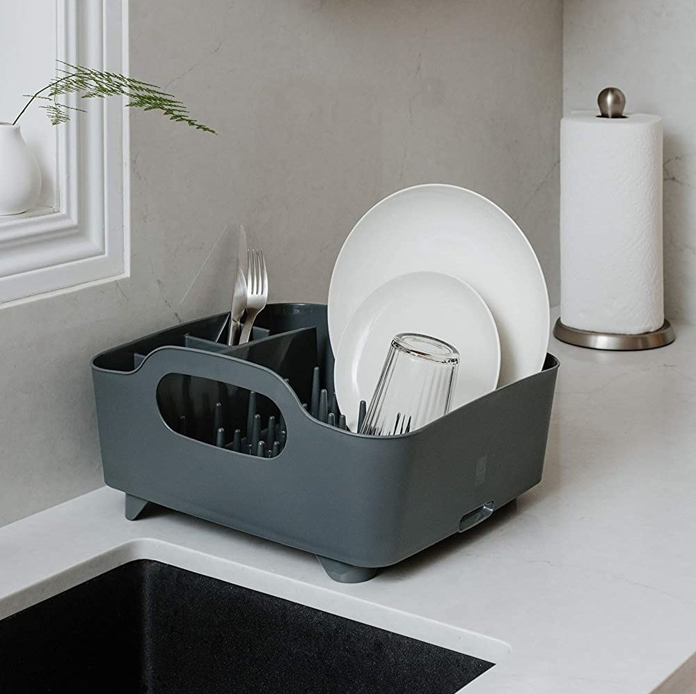 A large dish drying rack with handles perched on the edge of a sink