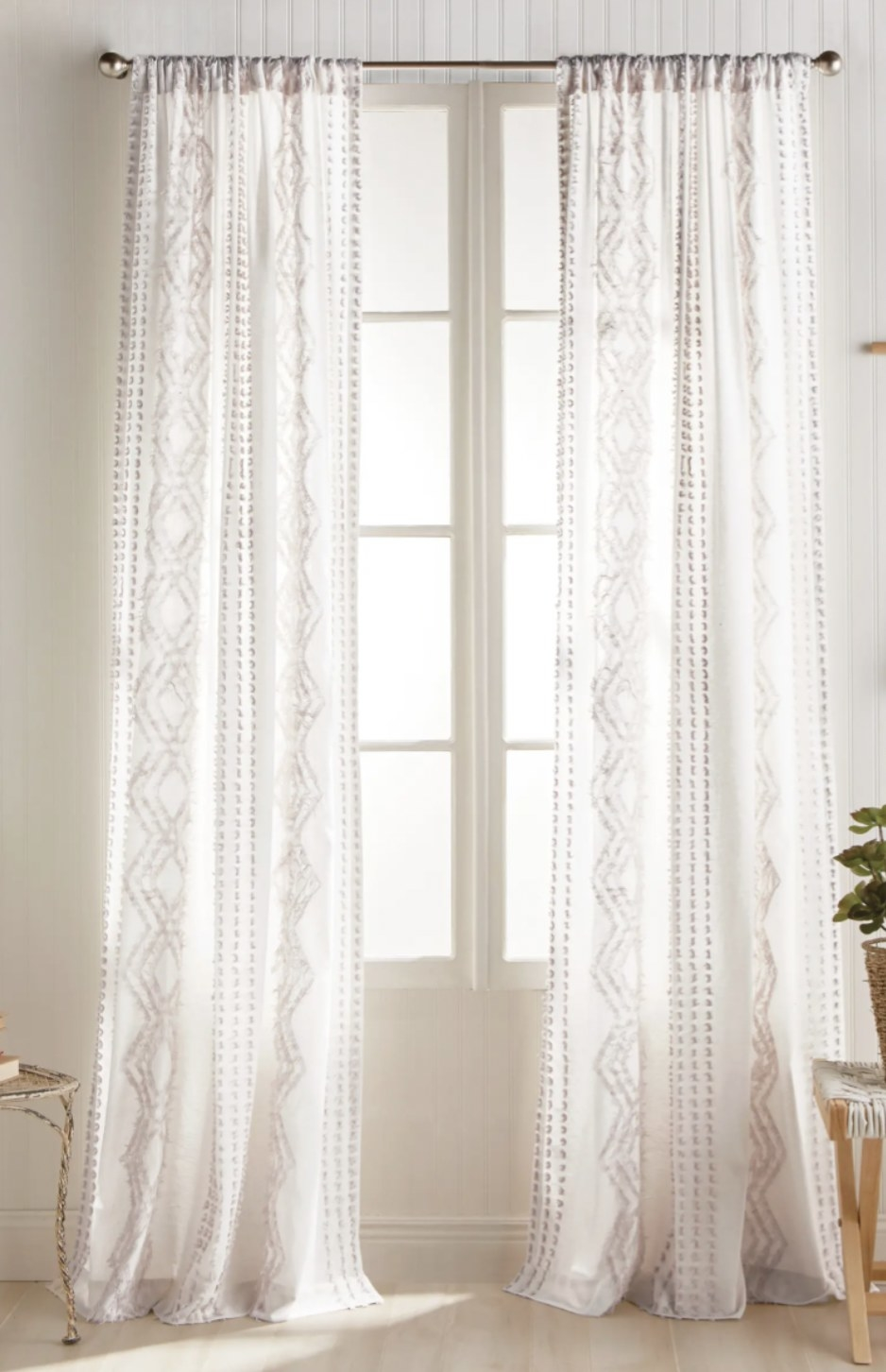 a set of white curtain panels handing in front of a window in a living roon