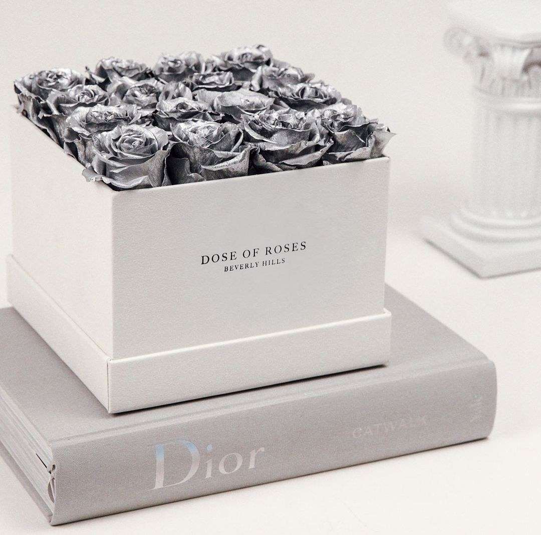 white square box with 16 metallic silver roses in the top of it