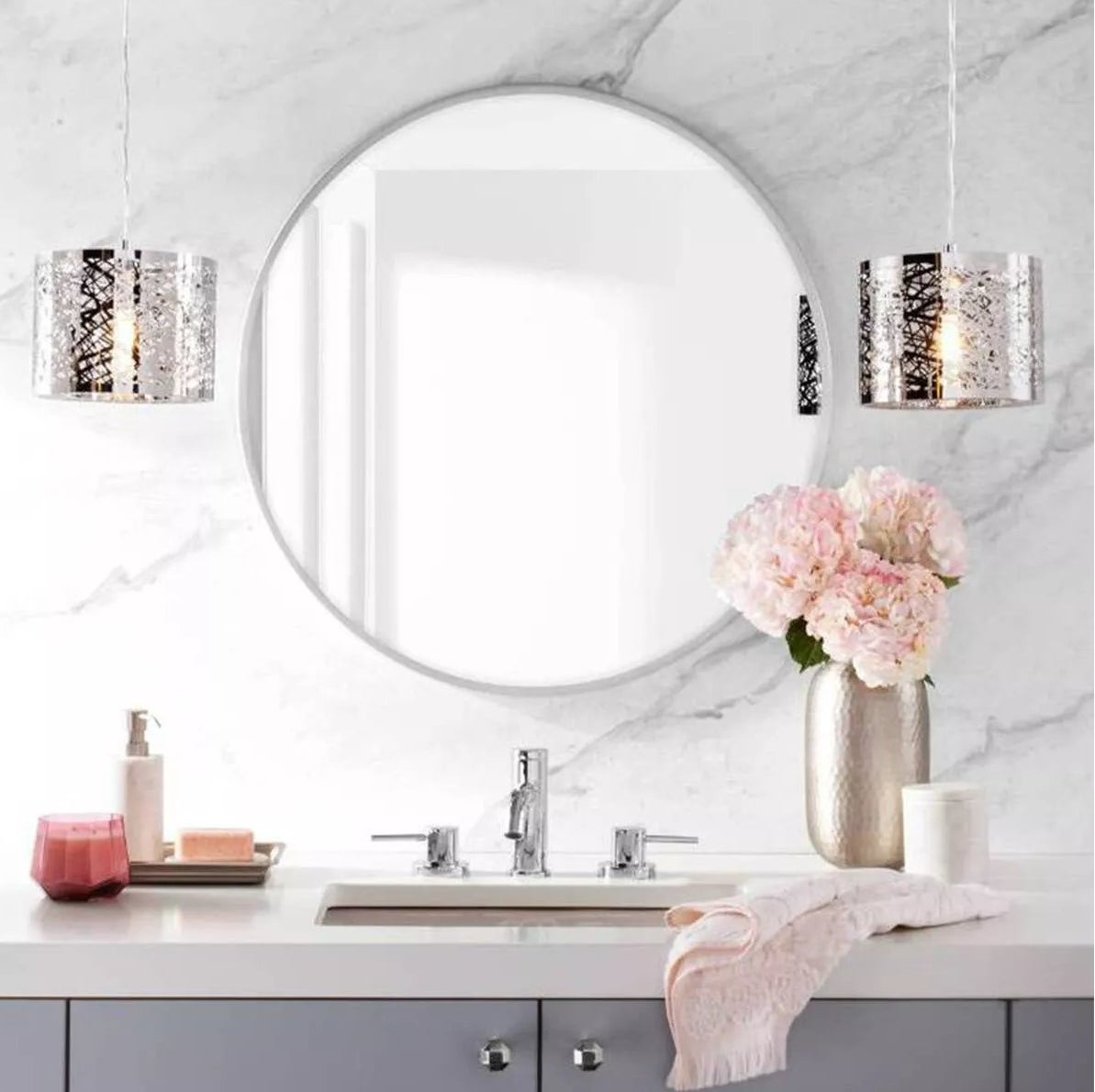 The round mirror with white trim hanging in a bathroom