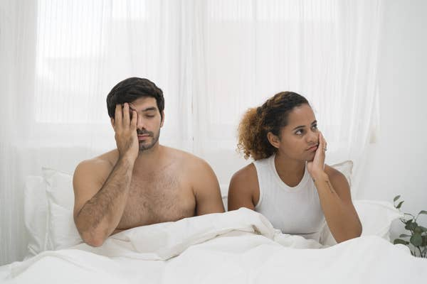 an unhappy couple in bed