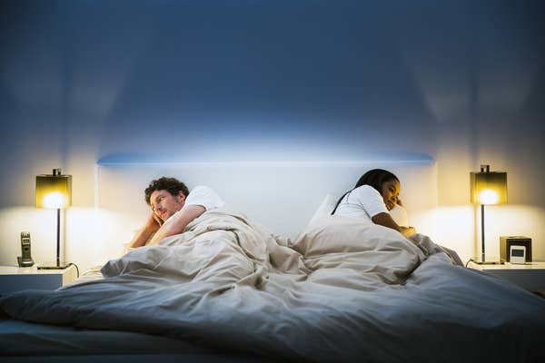 a couple looking away from each other in bed