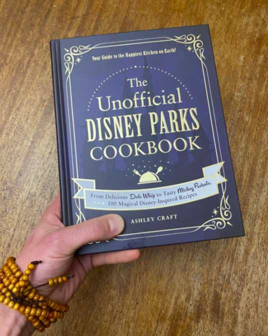 A customer review picture of them holding the Unofficial Disney Parks Cookbook
