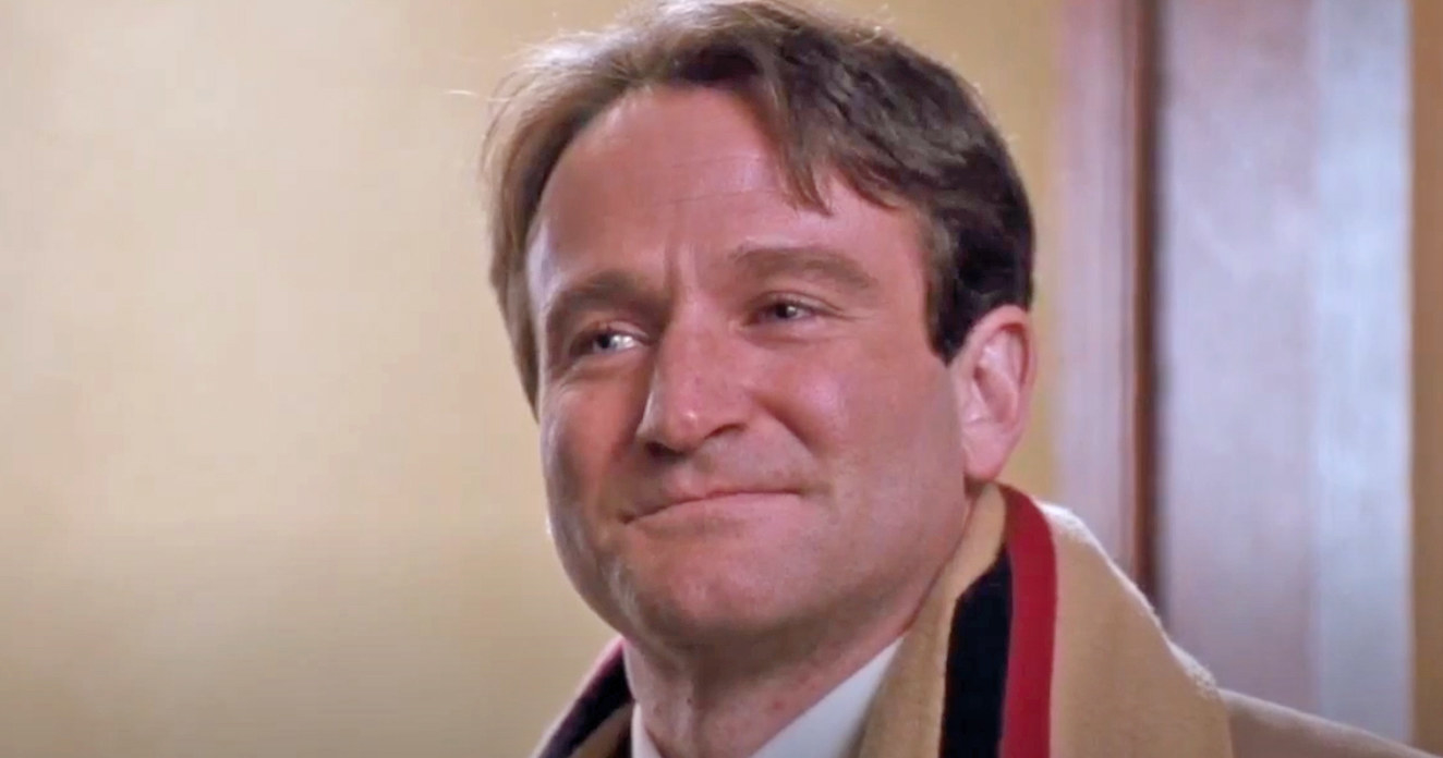 Robin Williams smiles softly while standing in a doorway as Mr. Keating