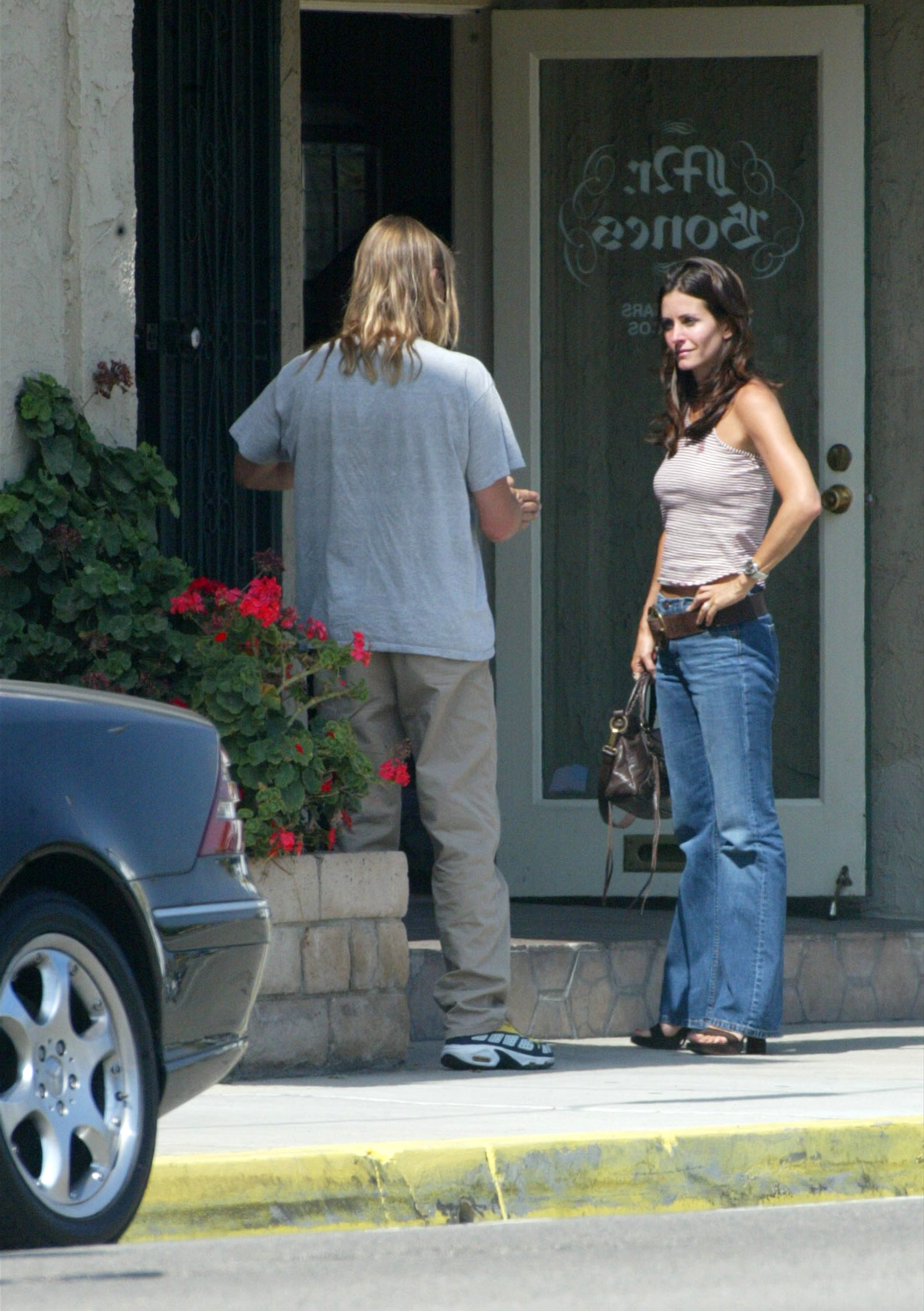 Courteney Cox in jeans and a tank top, her friend has his back facing the camera