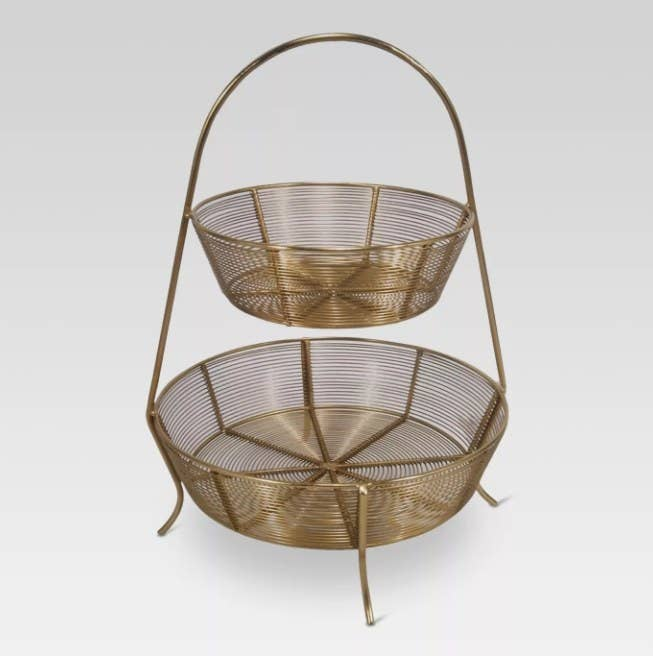 A two-tier, gold-plated wire basket that can be used to store fruit and vegetables
