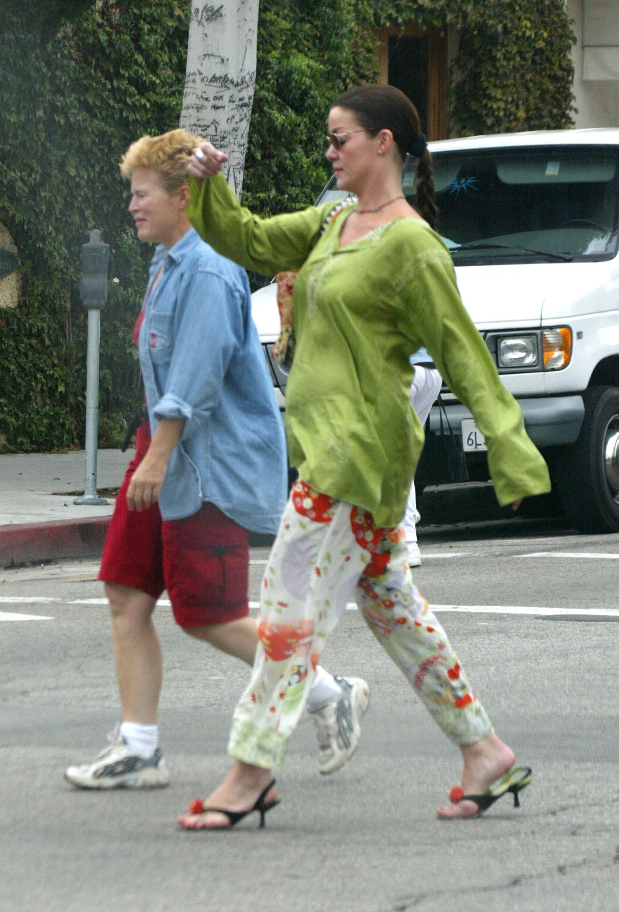 Claudia Christian in a very fun outfit walking with a friend