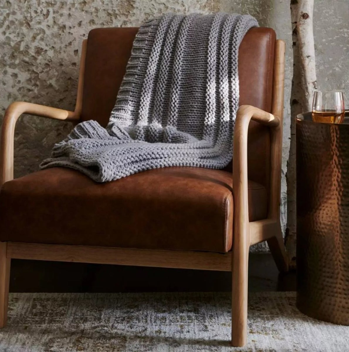 The brown leather armchair with a light wooden frame in a living room