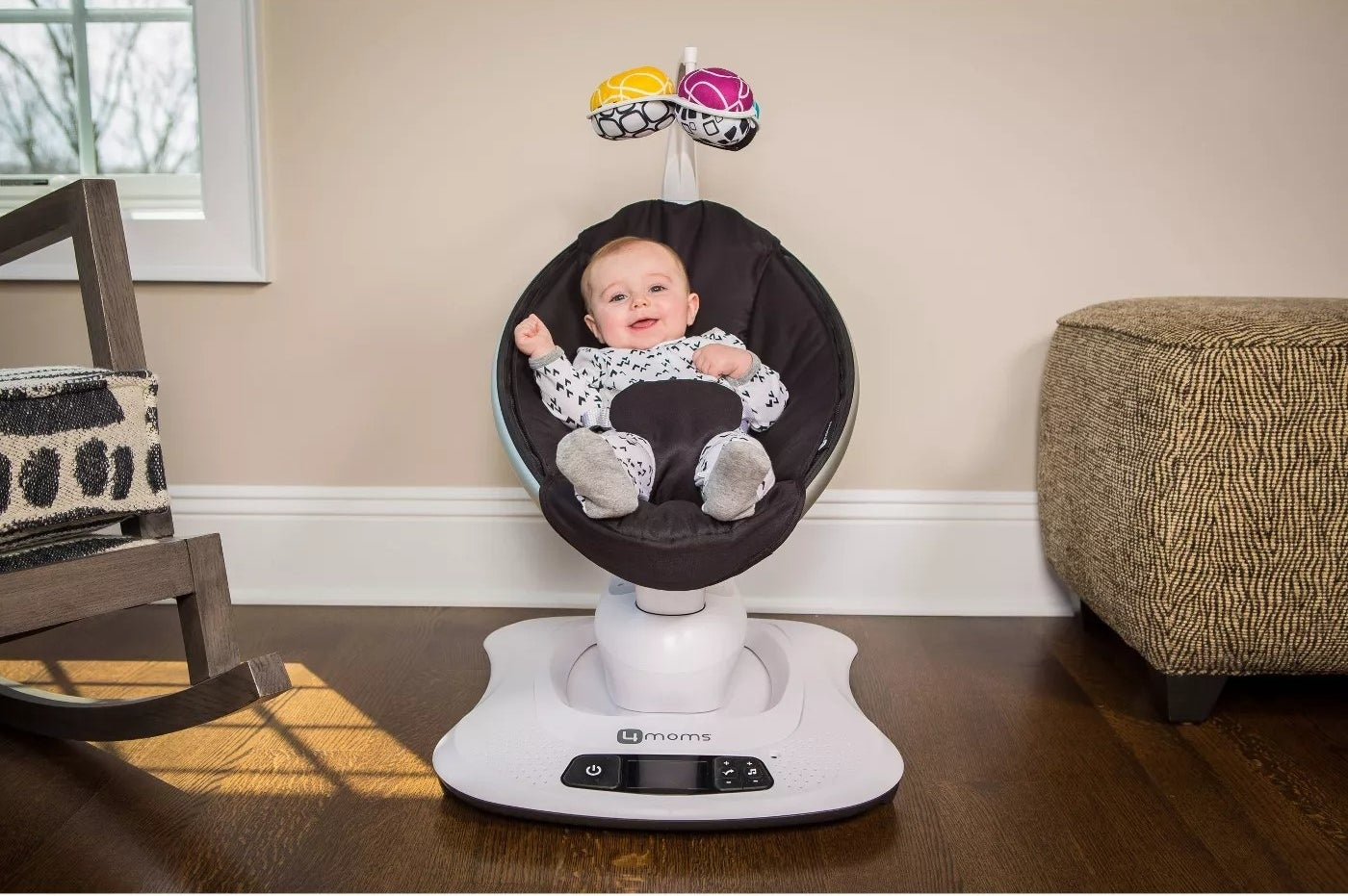 A baby smiling while sitting in the mamaRoo