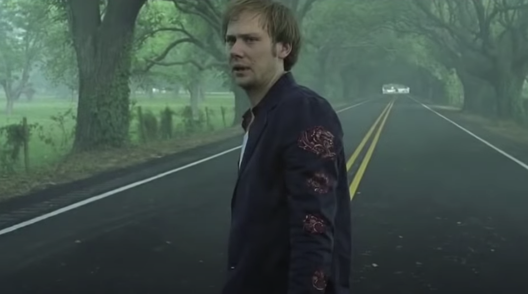 Jimmi Simpson standing in the middle of a road surrounded by trees as Phineus