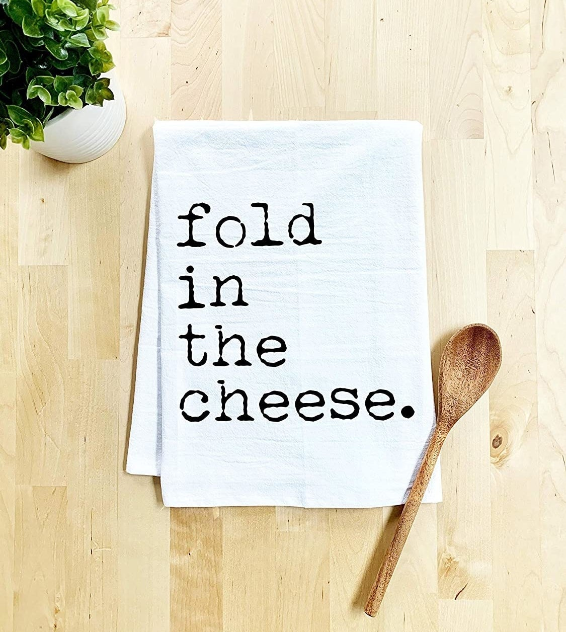 """white towel that reads """"fold in the cheese"""""""