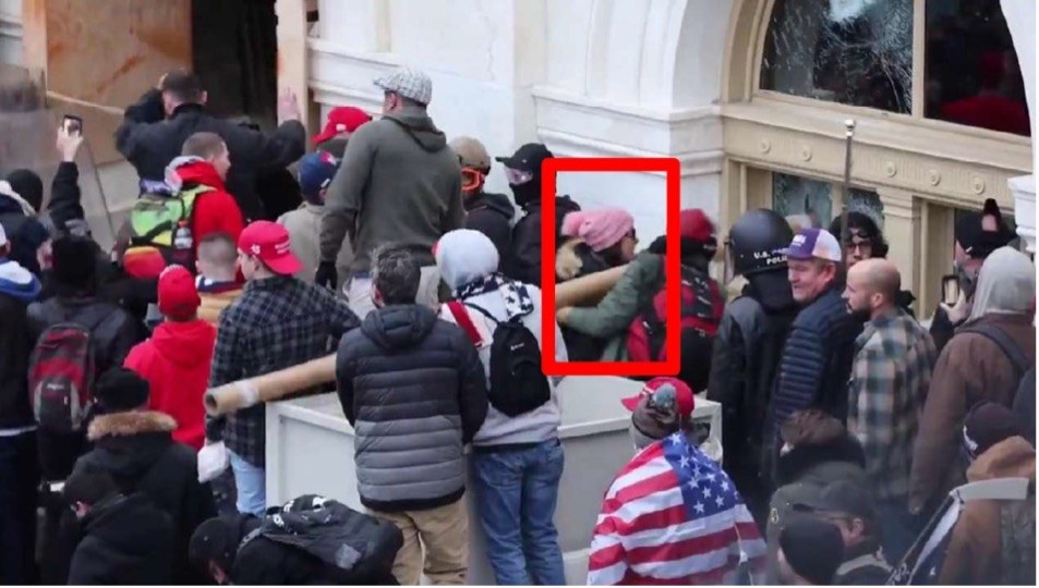A woman in a pink hat and others ramming a window at the Capitol