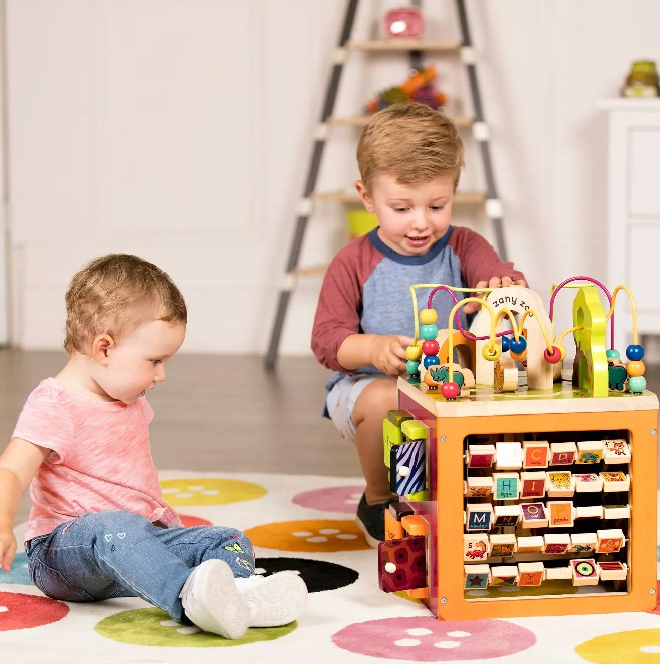 A baby and a toddler playing with the activity cube with multiple surfaces and games