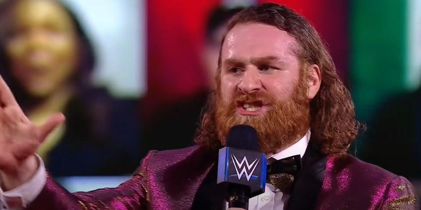 Sami Zayn speaking on WWE microphone in a purple suit
