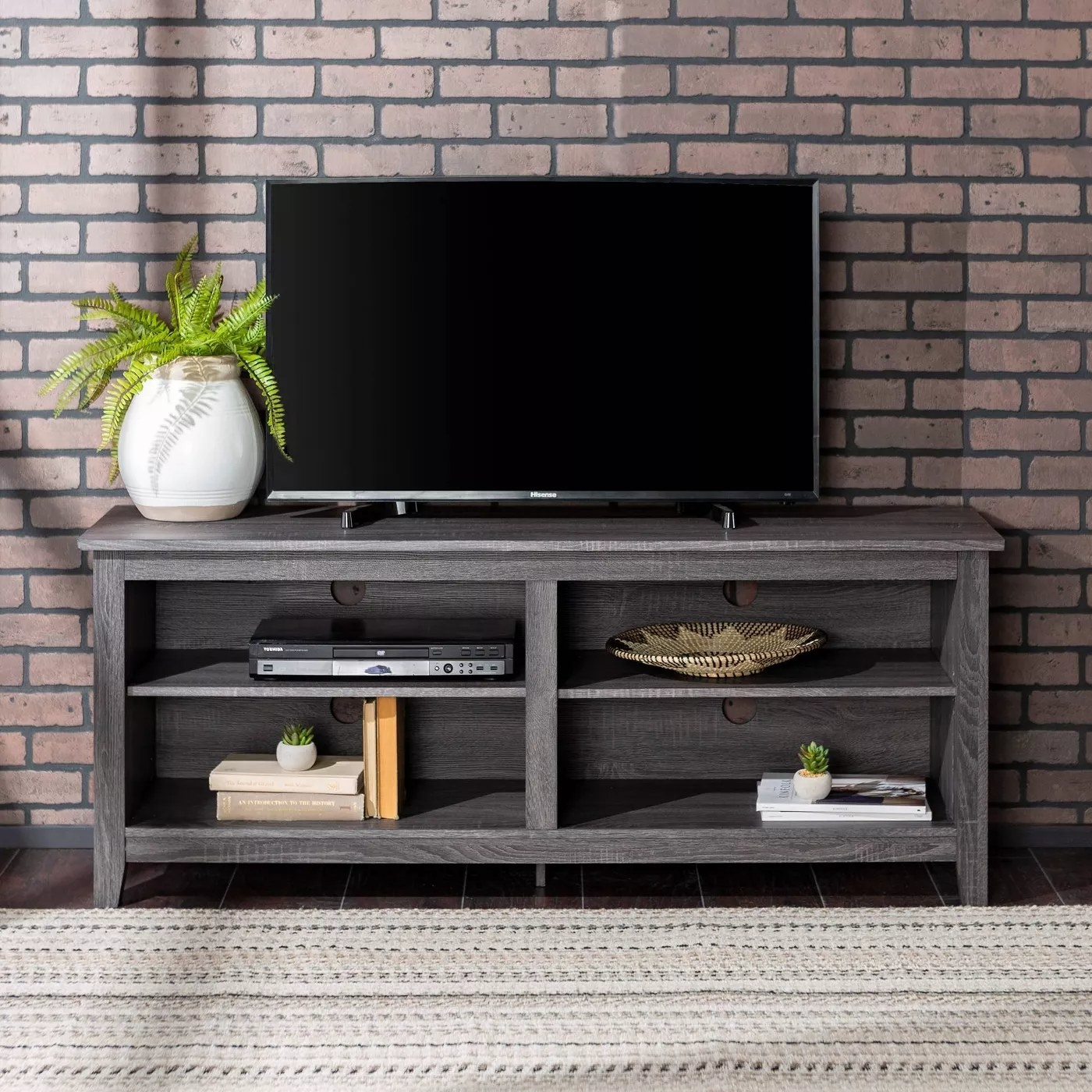 The wooden TV stand with four open shelves supporting a large flatscreen TV