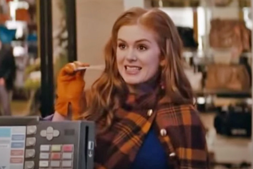 Isla Fisher holding up a credit card at a store checkout as Rebecca