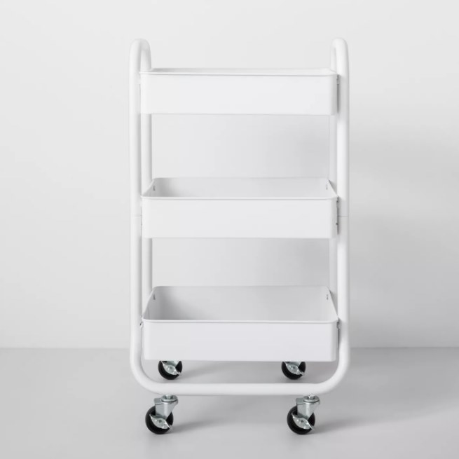 A three-tier metal rolling cart in white