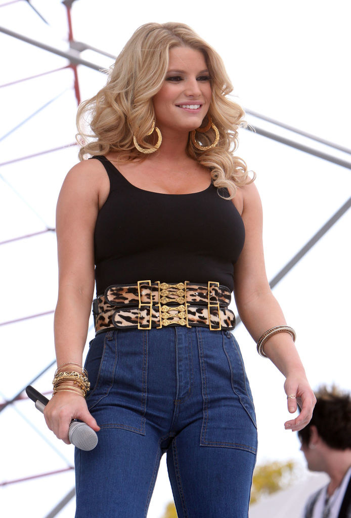 Jessica performing in Texas wearing high-waisted jeans and a tight camisole top that show off her curves