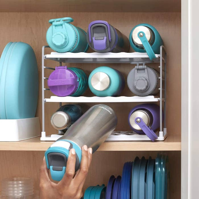 Model placing water bottle on storage rack in cabinet