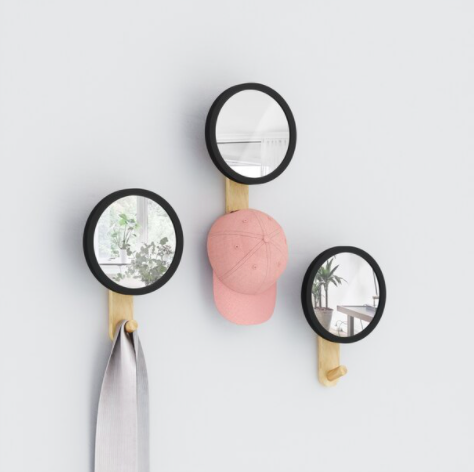 A trio of circular wall mirrors with tiny hooks at their base