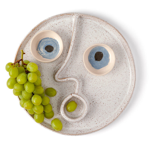 the platter with eyes that are small bowls and a divider down the center sculpted into a nose and round mouth, holding grapes
