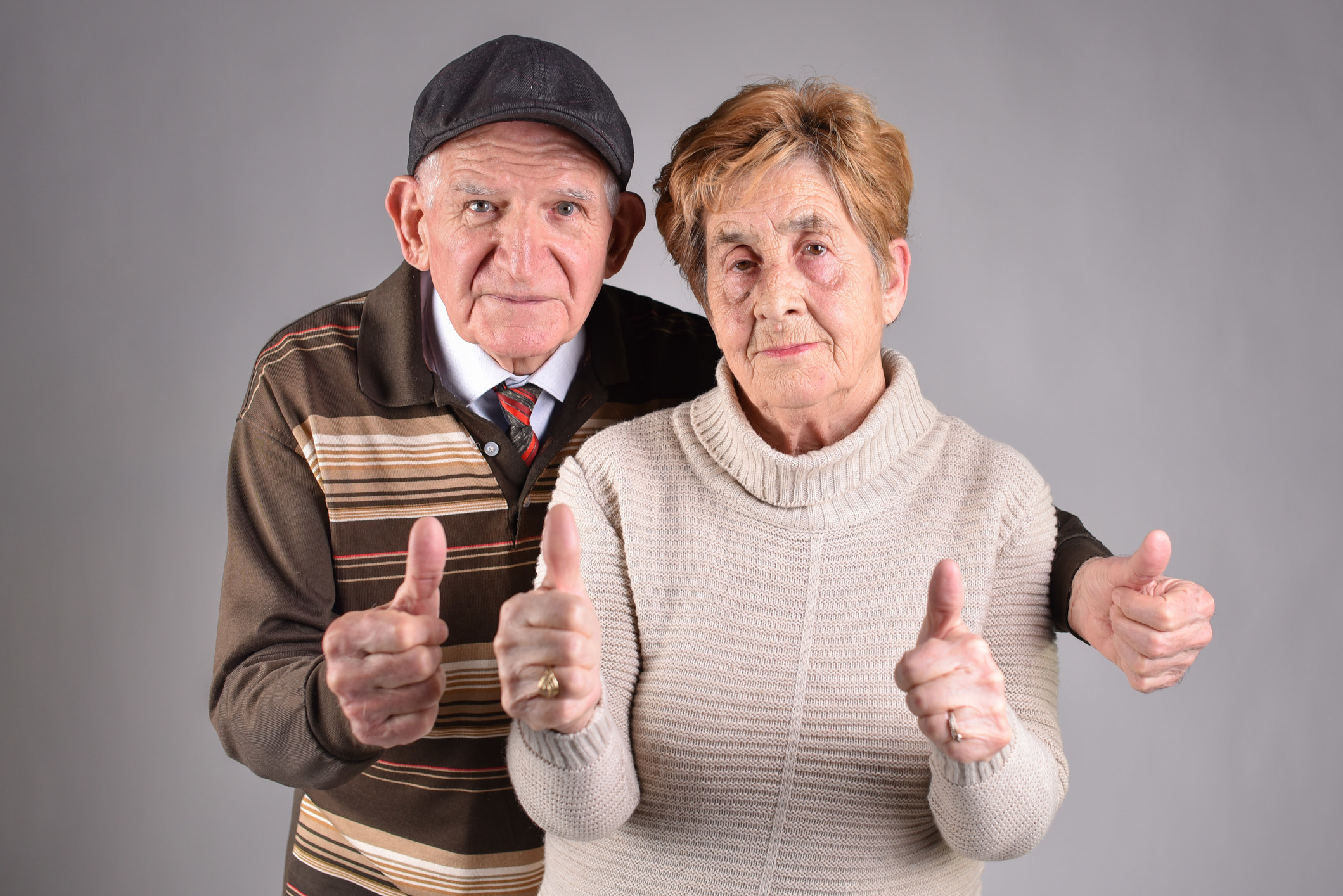 two old people giving thumbs up
