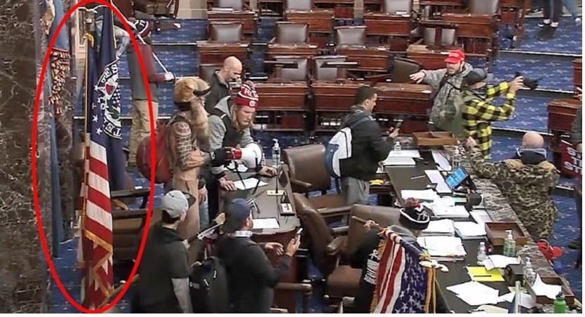 Several rioters stand in the US Senate chamber taking photos