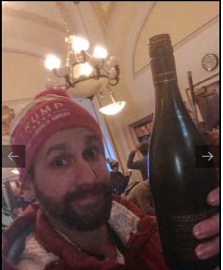 Riddle wears a Trump and holds a wine bottle up to the camera in the Capitol