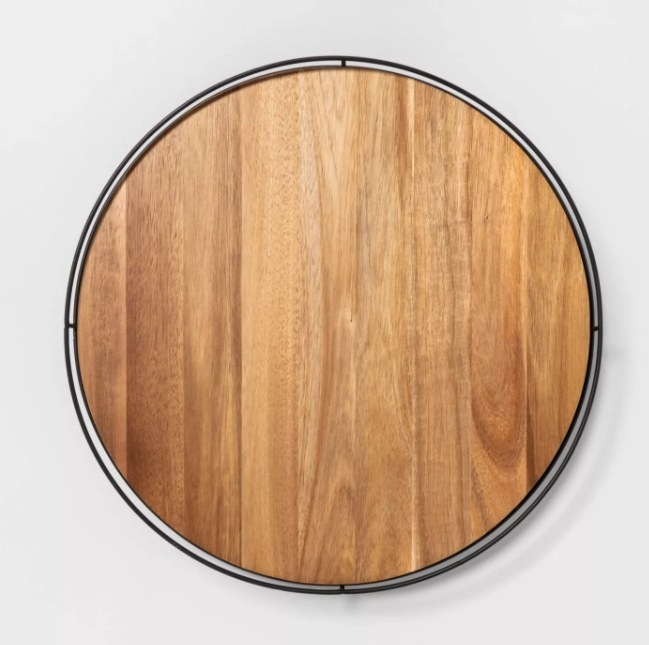 A circular wooden lazy susan that can store food items.