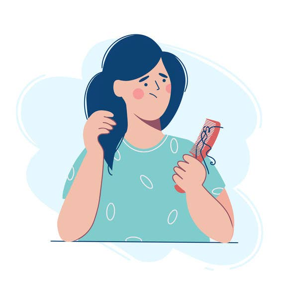 A woman is holding a comb with a lock of hair, she is upset because of hair loss.