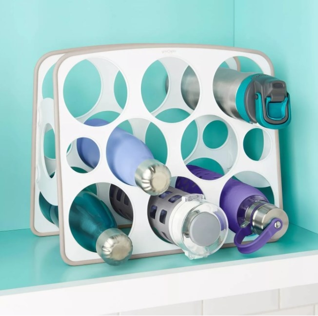 "A water bottle stand organizer that can hold drinking straws and eight bottles that are 3.5"" wide"