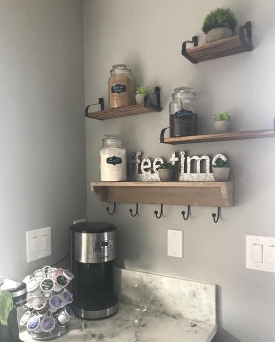 Reviewer's picture of the three wooden wall shelves holding kitchen jars and decorative signs