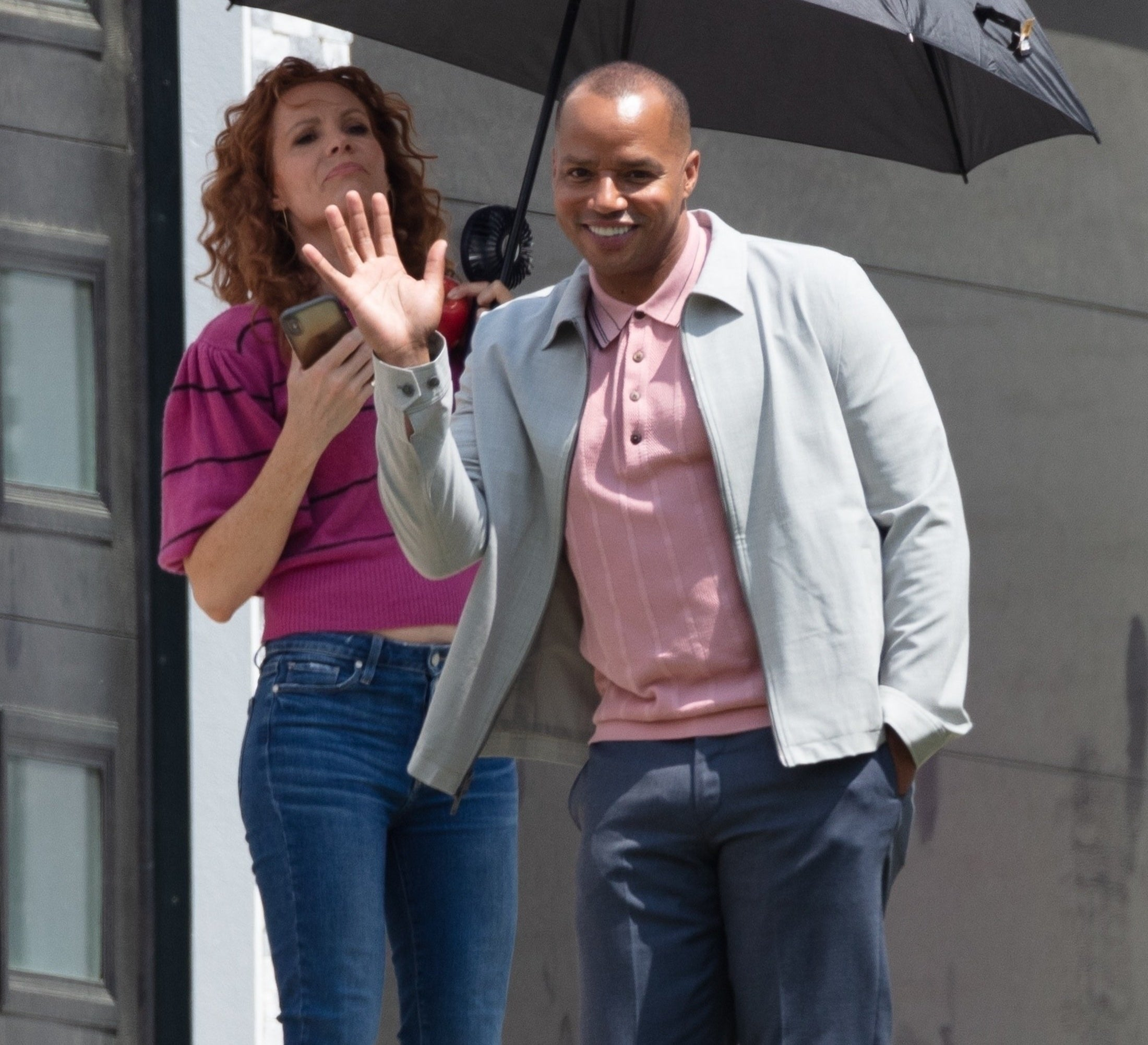 Donald Faison waving on set as someone holds an umbrella over his head