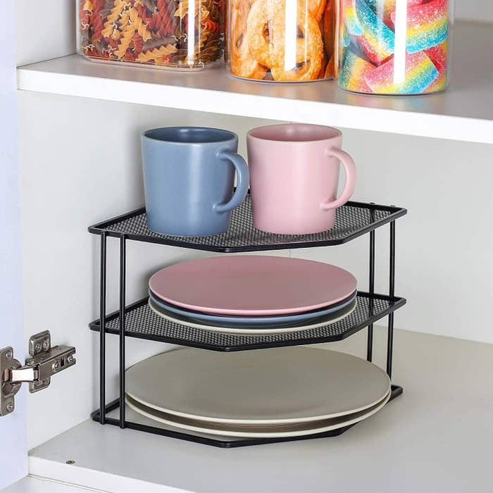 Dishes and cups placed on corner shelf in cabinet